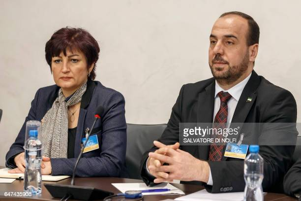 Syria's main opposition High Negotiations Committee leader Nasr alHariri flanked by Alise Mofrej member of the Syrian Women's Initiative for Peace...