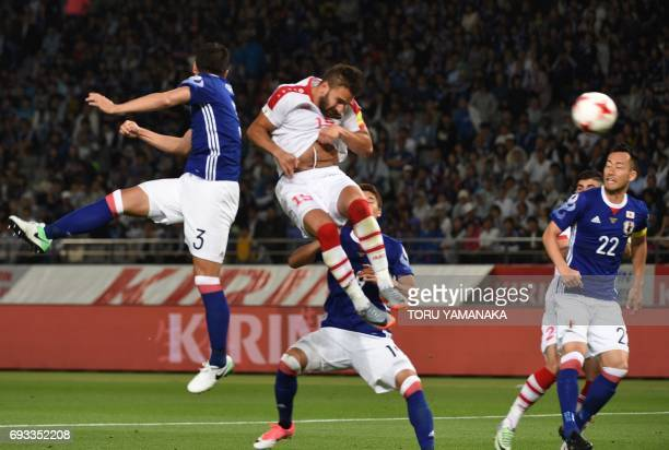 CORRECTION Syria's midfielder Mardik Mardikian heads the ball to score a goal past Japan's defender Gen Shoji and defender Maya Yoshida during their...