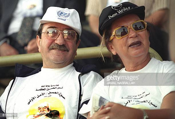 Syria's number one comedian Duraid Laham sits next to an unidentified woman at Amman's AlHussein Sports City 22 October 1999 Laham joined other top...