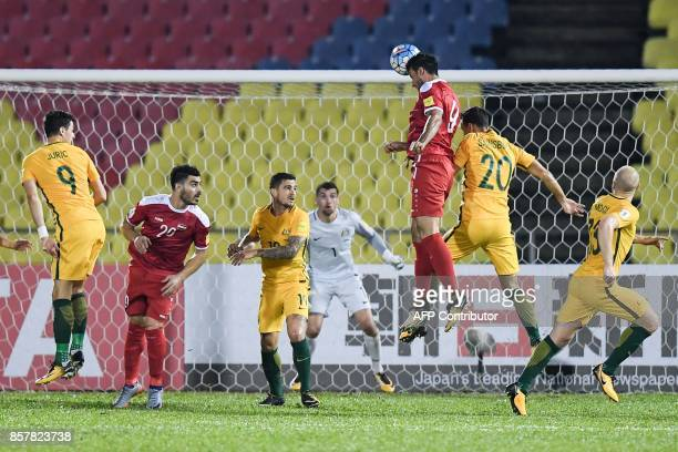 Syria's Omar Alsoma heads the ball during the 2018 World Cup qualifying football match between Syria and Australia at the Hang Jebat Stadium in...