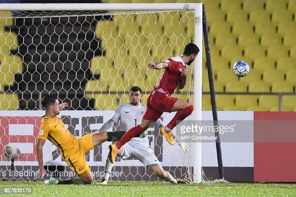Syria's Omar Khrbin shoots towards goal in front of Australia's Milos Degenek and goalkeeper Mathew Ryan during the 2018 World Cup qualifying...