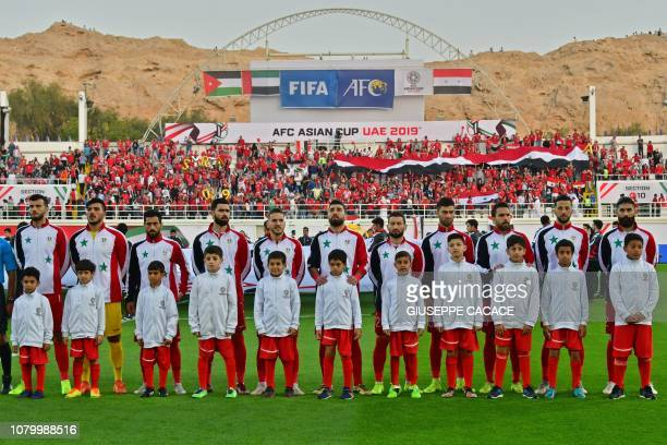 Syria's players pose with mascots ahead of the 2019 AFC Asian Cup group B football match between Jordan and Syria at the Khalifa bin Zayed stadium in...