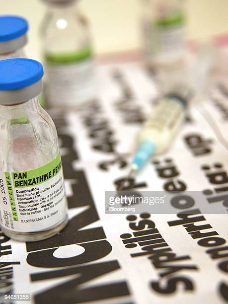 A syringe and penicillin vials used in the treatment of syphilis sit on top of a health warning poster at the Melbourne Sexual Health Centre in...