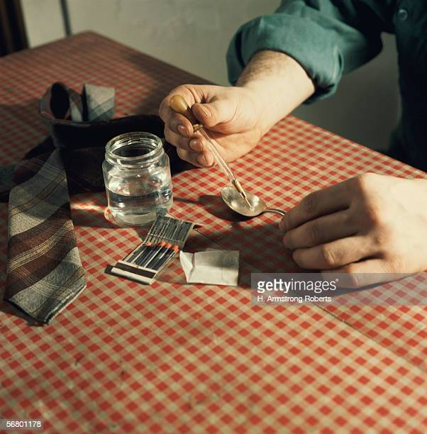 1970s: Syringe being filled with drugs from spoon.