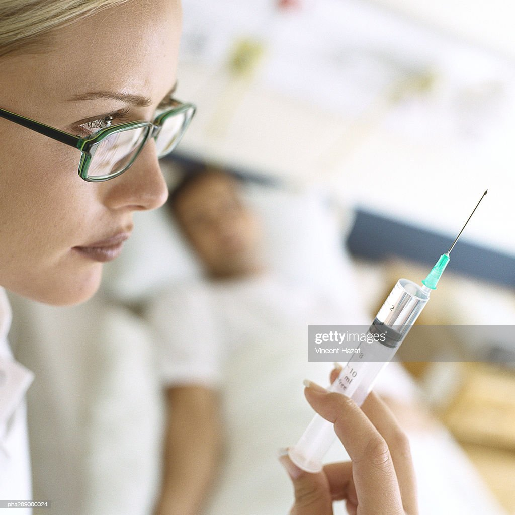 Syringe being held up in front of patient : Stockfoto