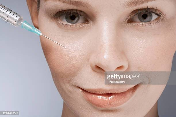 Syringe near woman's face, close-up