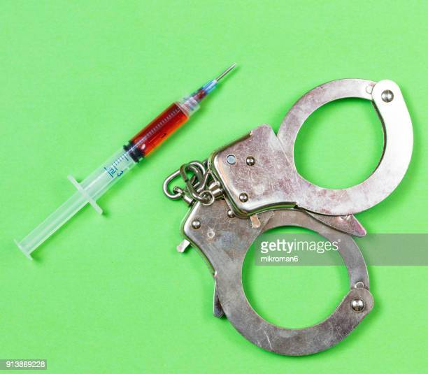 Syringe with narcotic and handcuffs. Medical concept