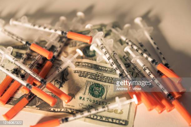 syringes covering two twenty dollar bills - economic stimulus stock pictures, royalty-free photos & images