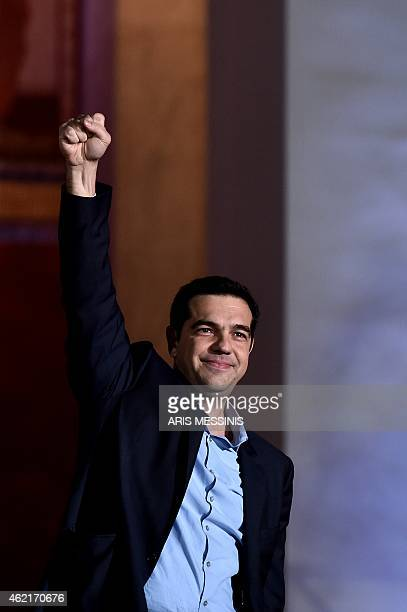 Syriza leader Alexis Tsipras raises his fist as he greets supporters following victory in the election in Athens on January 25 2015 The leftwing...