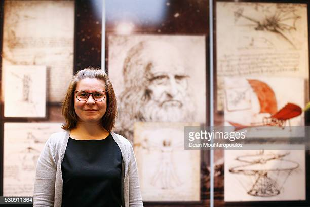 System Engineer Adina Cotuna poses in the Systems and Cost Engineering Division / The Concurrent Design Facility in front of Galileo sketches and...