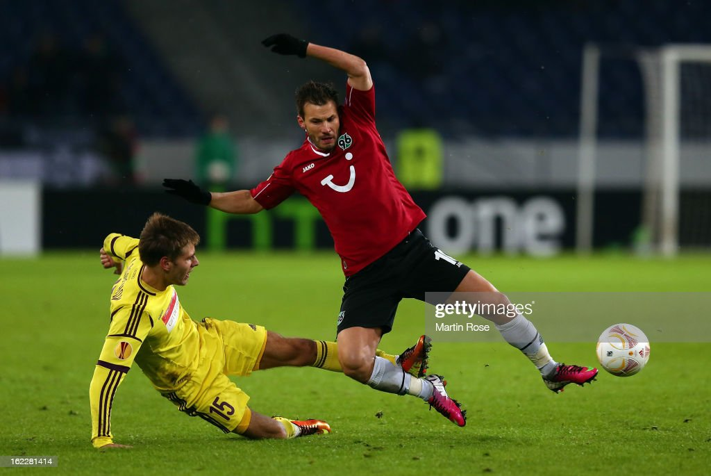 Szaboilcs Huszti (L) of Hannover and Arseni Logashov (R) of Makhachkala battle for the ball during the UEFA Europa League Round of 32 second leg match between Hannover 96 and Anji Makhachkala at AWD Arena on February 21, 2013 in Hannover, Germany.