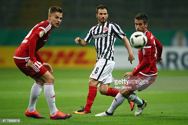 Szabolcs Huszti of Czech Republic is challenged by Max Christiansen and Stefan Lex of Ingolstadt during the DFB Cup Second Round match between...
