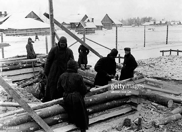 Szene in einem Kriegsgefangenenlager imWinter Sowjetische Gefangene bauen sichHolzbaracken als Unterschlupf 1941
