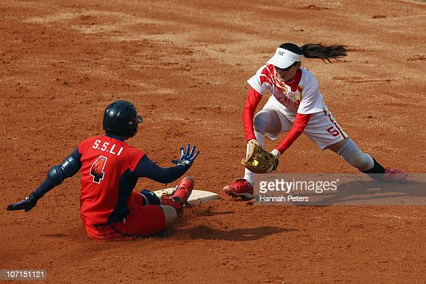 Szu Shih Li of Chinese Taipei dives into second base ahead of Chunxia Li of China in the semifinal match between China and Chinese Taipei at Tianhe...