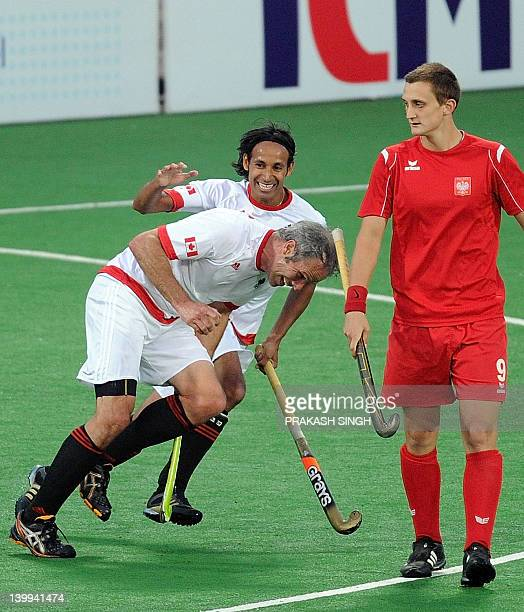 Szymon Oszyjcczyk of Poland watches as Rob Short of Canada celebrates a goal with teammate Ken Pereiraduring during the men's field hockey third...