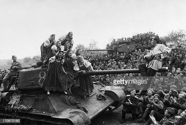 A t34 tank provides a suitable stage at the front for a group of kiev entertainers performing for the troops of the 3rd ukrainian front during world...