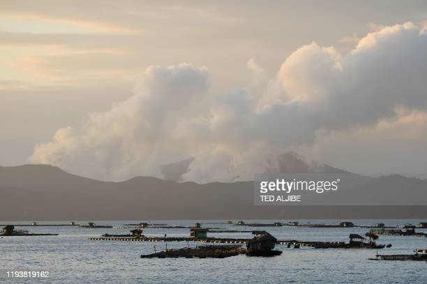 TOPSHOT Taal volcano spews steam as fish farms are seen from Laurel town Batangas province south of Manila on January 15 2020 Philippine authorities...