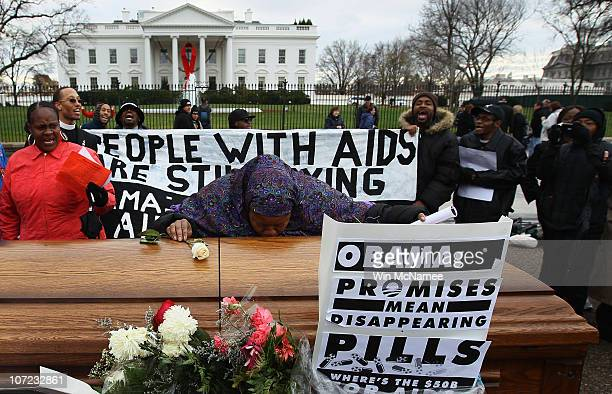 Taalibah Ines kisses a coffin as she places a rose on top of it while joining a group of AIDS activists marking World AIDS Day by holding a funeral...