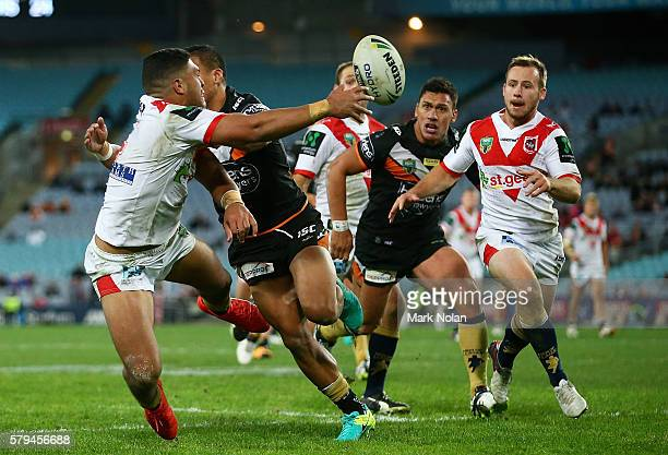 Taane Milne of the Dragons offloads to set up a try for Adam Quinlan of the Dragons during the round 20 NRL match between the St George Illawarra...