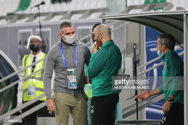 Taawoun coach Patrice Carteron greets his Duhail counterpart Walid Regragui during the AFC Champions League group C match between Qatar's AlDuhail...