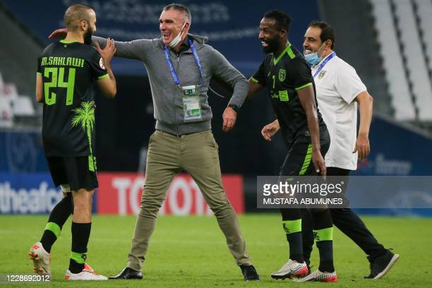 Taawoun's coach Patrice Carteron congratulates his players on their win during the AFC Champions League group C match between Qatar's AlDuhail and...