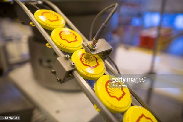 Tab seal caps for oil drums move along the production line after pressing at the Royal Dutch Shell Plc lubricants blending plant in Torzhok Russia on...