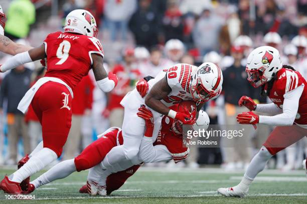 Tabarius Peterson of the Louisville Cardinals tackles Ricky Person Jr #20 of the North Carolina State Wolfpack in the first quarter of the game at...