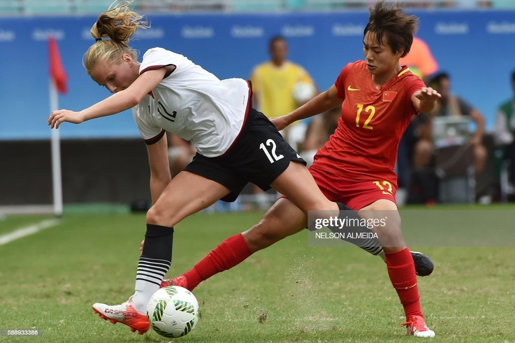 TOPSHOT - Tabea Kemme (L) of Germany vies for the ball with Shuang Wang of China during their Rio 2016 Olympic Games women's quarter-final football match at the Arena Fonte Nova Stadium in Salvador, Brazil, on August 12, 2016. / AFP / NELSON