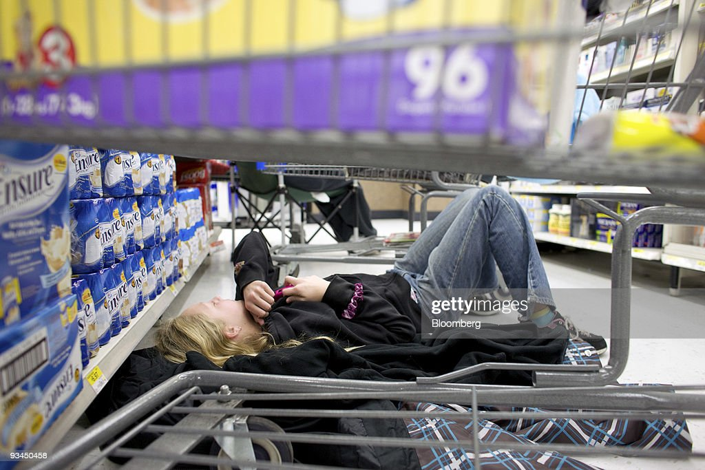Tabitha Taormina, 13, lays on the ground while waiting in line for laptop computers at a Wal-Mart Supercenter in Denver, Colorado, U.S., on Friday, Nov. 27, 2009. Shoppers gathered at Best Buy Co., Target Corp. and Toys 'R' Us Inc. stores from New Jersey to Texas well before midnight yesterday to take advantage of Black Friday deals on televisions, laptops and robot hamsters. Photographer: Matthew Staver/Bloomberg via Getty Images