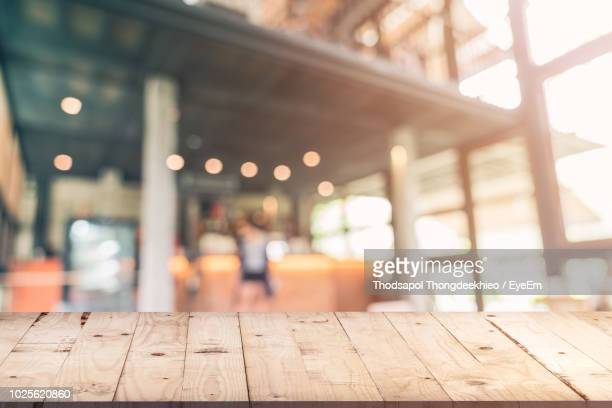 table against illuminated lights at cafe - table surface stock photos and pictures