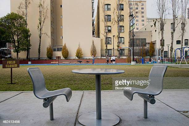 A table and chairs are seen as men play basketball in Boeddeker Park in the Tenderloin district of San Francisco California US on Thursday Jan 15...