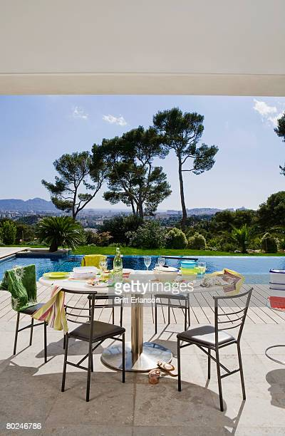 table and chairs by poolside. - after party mess stock pictures, royalty-free photos & images