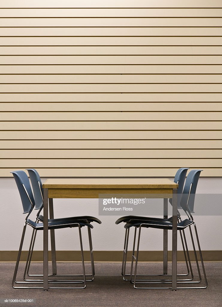 Table and chairs by wooden wall, side view : Foto stock