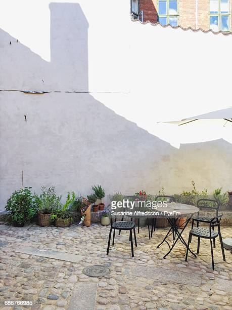 Table And Chairs On Paved Yard Of House