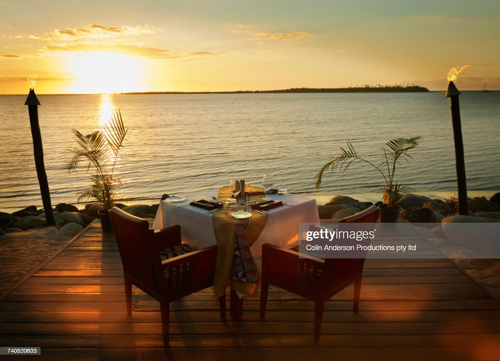 Table and chairs on waterfront at sunset : Stock Photo