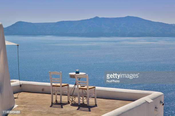 Table and chairs overlooking the Aegean Sea in the village of Firostefani on Santorini Island Greece