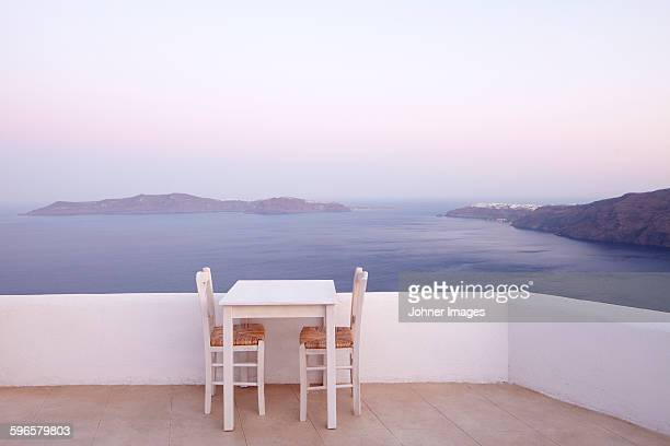 Table and chairs, sea on background