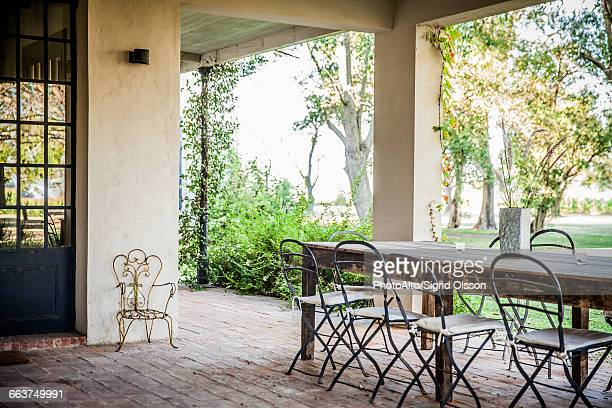 Table and chairs set on house veranda