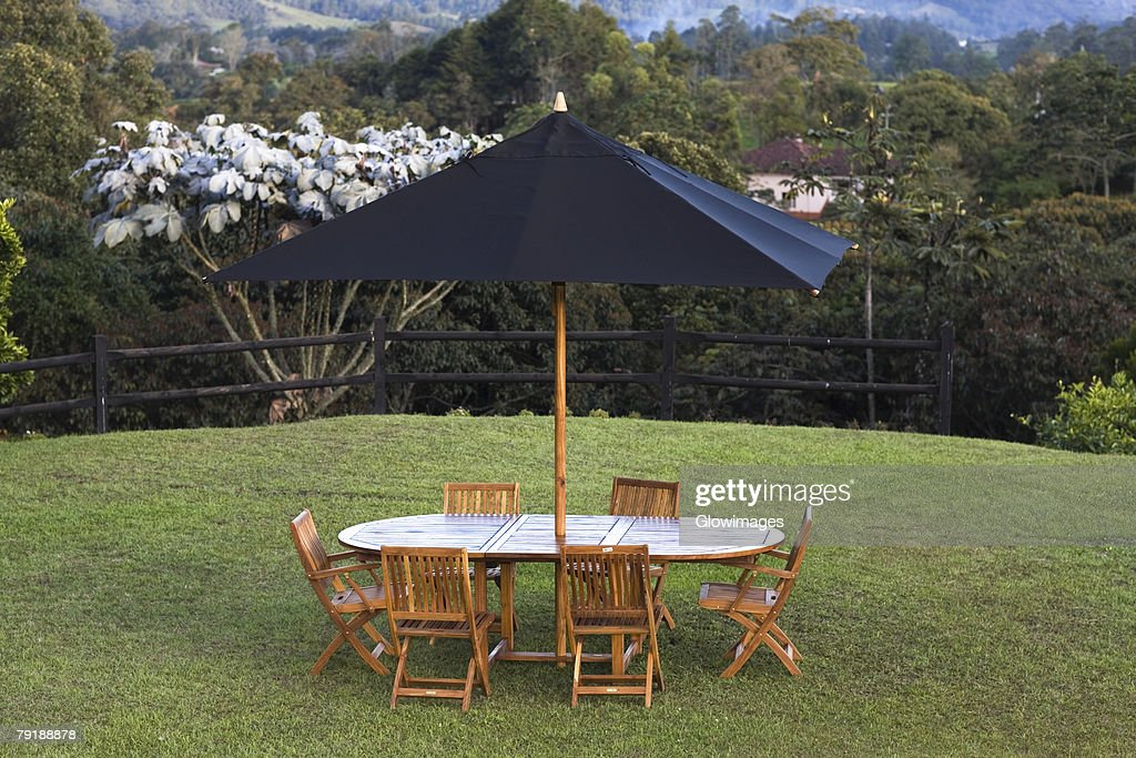 Table and chairs under a patio umbrella in a lawn : Foto de stock