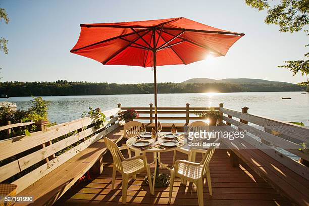 Table and chairs with umbrella on a deck beside a lake