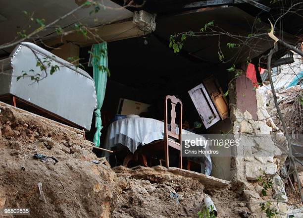 A table and couch sit precariously on the edge of a house split in half in the aftermath of an earthquake January 15 2010 in Port au Prince Haiti...