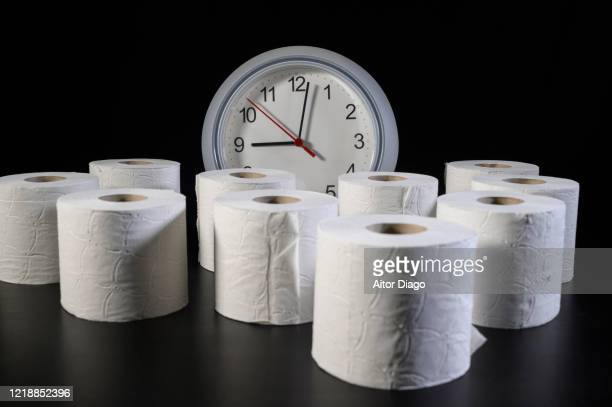 a table appears full of full rolls of toilet paper with a clock in the background. - hemorroide fotografías e imágenes de stock