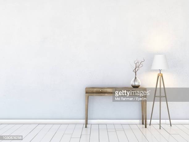 table by illuminated electric lamp against white wall - electric lamp stock pictures, royalty-free photos & images