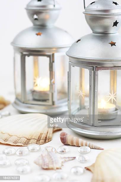 Pièce maîtresse de Table avec des lanternes et des coquillages sur blanc