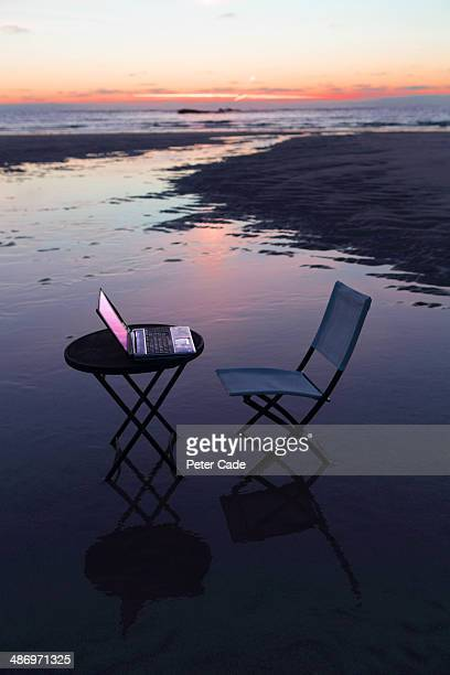 table, chair and laptop on beach at sunset