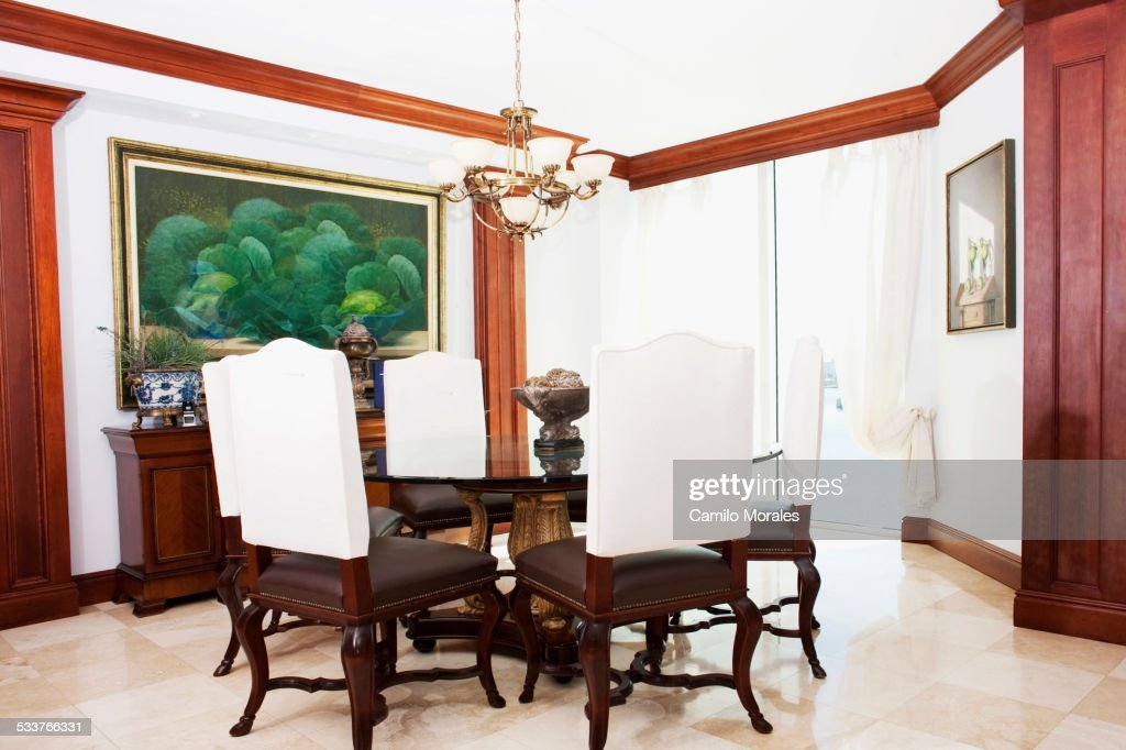 Table, chairs and wall art in ornate dining room : Foto stock