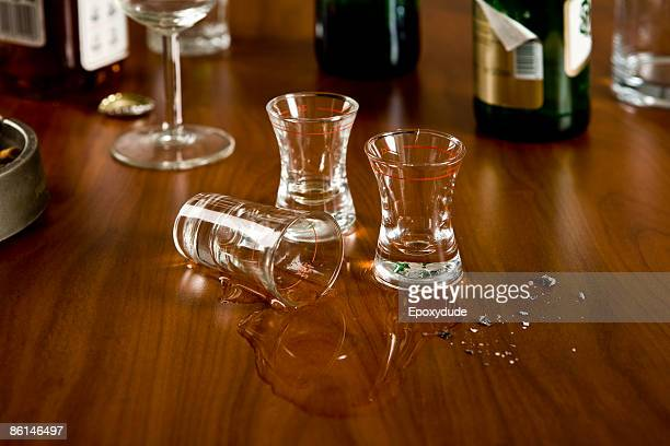 A table cluttered with shot glasses and bottles