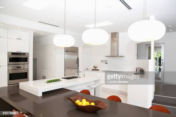 Table, countertops and light fixtures in modern kitchen