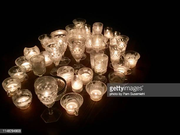 table covered in votive candles in clear glasses - cero foto e immagini stock