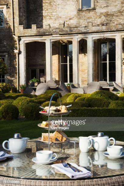 A table in a garden outside an old house, with cake stand and a selection of cakes and sandwiches set for a traditional afternoon tea.